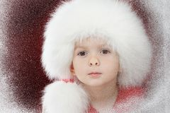 Merry Christmas little sad child on window looking at the winter. Kid and snowfall. Royalty Free Stock Photo