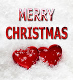 Merry Christmas Love Hearts in Snow. Merry Christmas message with two red love hearts on a snow background Royalty Free Stock Photos