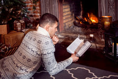 Merry Christmas. man resting by the fireplace reading a book at home Royalty Free Stock Photos