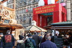 Merry Christmas Manchester Christmas market. Manchester,England - November 16th 2015:Manchester Christmas market visitors walkinh underneath a Merry Christmas Stock Image