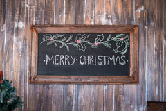 Merry Christmas on message note with wooden background. Merry Christmas, Christmas decoration with merry christmas on blackboard over wooden background Royalty Free Stock Photo