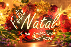 Merry Christmas message in Portuguese. Flowers and lights background. Stock Photography