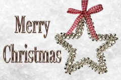 Merry Christmas Message With Silver Star. Merry Christmas greeting message with a silver star with red and white ribbon bow against a frozen snow backdrop Stock Photo