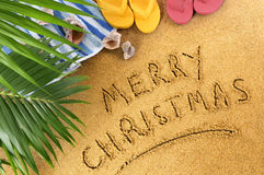 Merry Christmas message written in sand on a sunny tropical beach, Christmas holiday vacation concept royalty free stock photo