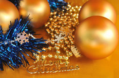 Merry christmas metal text and ornaments on gold background Stock Photo