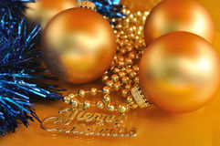 Merry christmas metal text and ornaments on gold background Royalty Free Stock Photography