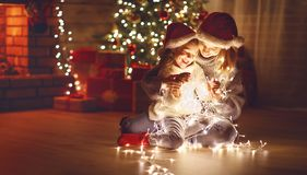 Merry Christmas! mother and child daughter with glowing garland Royalty Free Stock Images