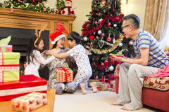 Merry Christmas Mum!. Chinese family enjoying Christmas in their home. The children are cuddling their Mother who is sitting by the Christmas tree with presents royalty free stock images