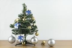 Merry Christmas and New Year concept, small Christmas tree is decorated with ornaments on wooden table and white background. stock photo