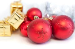 Merry Christmas, New Year, gifts in gold boxes, red Christmas balls in the right corner. White background royalty free stock photos
