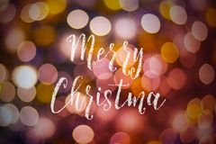Merry Christmas and New Year typographical on pink gold sparkle. Bokeh or defocus with Xmas card text stock photography