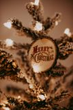 Merry Christmas Ornament on Tree. Warm feeling, frosted white tree, round rustic wood ornament with ornate text royalty free stock photo