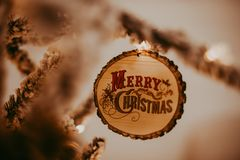 Merry Christmas Ornament on Tree. Warm feeling, frosted white tree, round rustic wood ornament with ornate text stock photos