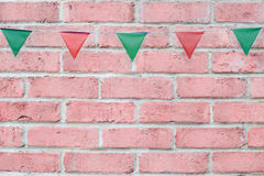 Merry Christmas Party flags bunting hanging on vintage pastel pink brick wall background on x`mas eve holiday event. Stock Photos
