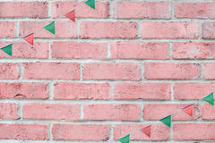 Merry Christmas Party flags bunting hanging on vintage pastel pink brick wall background on x`mas eve holiday event. Royalty Free Stock Images