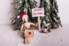 Merry Christmas picket sign held by wooden jointed wearing Santa hat holding a present on winter scene stock photo