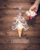 Merry Christmas postcard. Magical white Christmas tree and angel in the hand on a background of the brown planks Stock Image