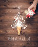 Merry Christmas creative postcard. Merry Christmas postcard. Magical white Christmas tree and angel in the hand on a background of the brown planks Royalty Free Stock Photography