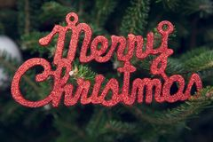 Merry christmas red gleaming inscription on a fir tree. Merry christmas red gleaming inscription on a Christmas tree. Dark green Christmas or New Year background Stock Photography