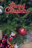 Merry christmas red gleaming inscription on a decorated fir tree. Merry christmas red gleaming inscription on a Christmas tree decorated with red baubles and Stock Photography