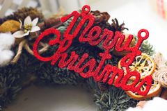 Merry christmas red gleaming inscription. On a pine wreath background Royalty Free Stock Photo