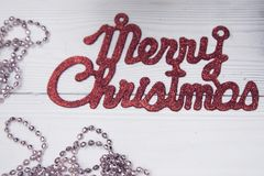 Merry christmas red gleaming inscription on a whitewooden background. Merry christmas red gleaming inscription with a chain of pink beads on a white wooden Royalty Free Stock Photography