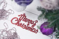 Merry christmas red gleaming inscription on a whitewooden background. Merry christmas red gleaming inscription with a chain of pink beads and unfocused fir tree Stock Images