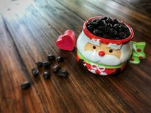 Merry Christmas, Red heart and coffee beans in Cute Santa Claus Cup. On the wooden table. Vintage style and Low light Stock Images