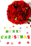 Merry christmas and red rose in vase. Merry christmas sign and red rose in glass vase on white background royalty free stock photo