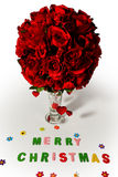 Merry christmas and red rose in vase. Merry christmas sign and red rose in glass vase on white background stock photography