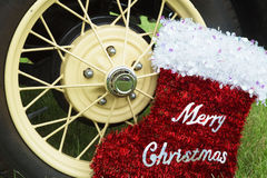 Merry Christmas red stocking decoration and a car's wheel,xmas. Merry Christmas red stocking decoration and  yellow and black car's wheel,green grass,xmas Stock Images