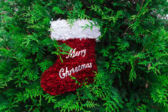 Merry Christmas red stocking decoration and a car`s wheel,xmas. Merry Christmas red stocking decoration and  yellow and black car`s wheel,green grass,xmas Stock Photo