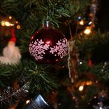 Merry Christmas!. A red Christmas tree ball with glitter in a Christmas tree Royalty Free Stock Photo
