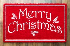 Merry Christmas Red Welcome Mat On Wood Floor Background.  royalty free stock image