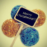 Merry christmas with a retro effect. Sentence merry christmas written in a blackboard label with some christmas balls with a retro effect Royalty Free Stock Image