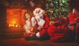 Merry Christmas! santa claus and  child girl at night at the Chr Stock Photos
