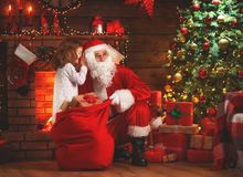 Merry Christmas! santa claus and  child girl at night at the Chr. Merry Christmas! santa claus and little child girl at night at the Christmas tree Royalty Free Stock Photo