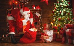 Merry Christmas! santa claus and  child girl at night at the Chr. Merry Christmas! santa claus and little child girl at night at the Christmas tree Stock Image