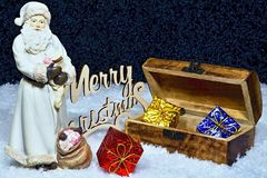 Merry Christmas - Santa Claus figure with a wooden box full of presents and an evening snow background. Santa Claus, snow background annd box with gifts Stock Photo