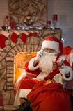 Merry Christmas. Santa Claus at home by the fireplace and Christ. Mas tree gives gifts stock image