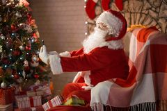 Merry Christmas. Santa Claus at home by the fireplace and Christ. Mas tree gives gifts stock photos