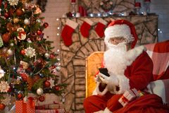 Merry Christmas. Santa Claus at home by the fireplace and Christ. Mas tree gives gifts royalty free stock photo