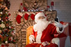 Merry Christmas. Santa Claus at home by the fireplace and Christ. Mas tree gives gifts stock images