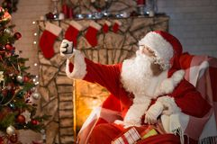 Merry Christmas. Santa Claus at home by the fireplace and Christ. Mas tree gives gifts royalty free stock photography
