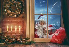 Santa Claus is knocking at window. Merry Christmas! Santa Claus is knocking at window. Room decorated for holidays. View indoors home royalty free stock photos