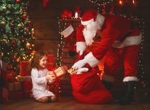 Merry Christmas! santa claus and  child girl at night at the Chr. Merry Christmas! santa claus and little child girl at night at the Christmas tree Royalty Free Stock Image