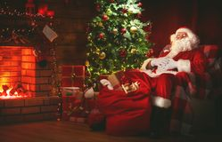 Merry Christmas! santa claus near the fireplace and tree with gi Stock Photography