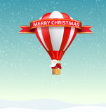 Merry Christmas Banner with Santa Claus riding hot air balloon. In snowy day with a ribbon and lots of gift, present, candy. Negative space below can be used royalty free stock image