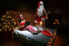 Merry Christmas. Santa Claus surfing on the bed while girlfriend watching laptop Royalty Free Stock Photos