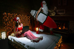 Merry Christmas. Santa Claus surfing on the bed while girlfriend watching laptop Royalty Free Stock Photo